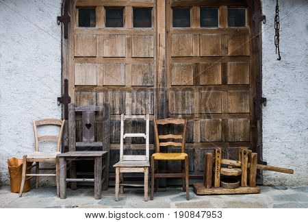 Vintage Chairs Lined Up Outside Wooden Doors Of Stone Outbuilding