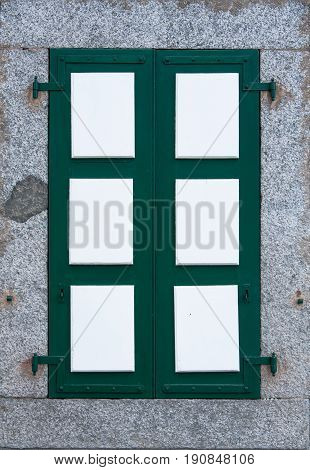 Window With Closed Green White Shutters In Stone Building Wall