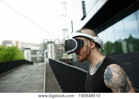 Virtual reality concept. Man wearing VR googles in city. Gaming beard tattooed male in black t-shirt near modern business building.