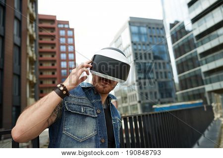 Virtual world concept. Internet VR life in big city. People playing outdoor in virtual reality. Man in casual wear use modern technology in the street. Brutal bearded guy use 3d glasses with internet.