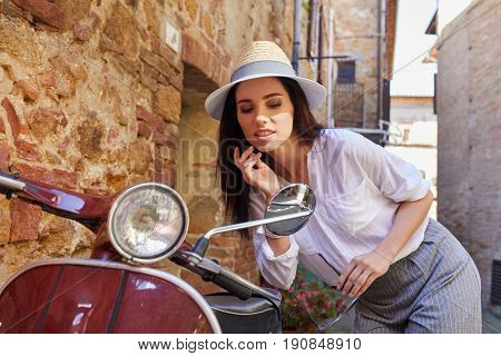 Hipster girl in Italy uses rearview mirror of scooter for doing her makeup