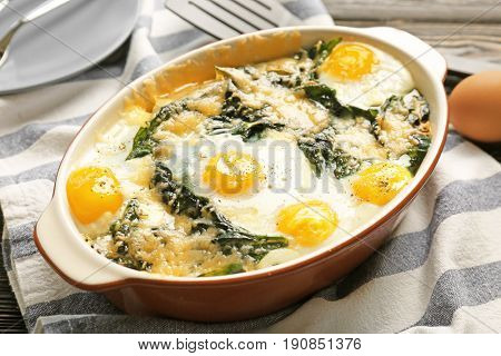 Baking dish with delicious cooked eggs Florentine on napkin, close up