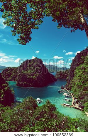 Elevated view of lagoon with boats surrounded by rocks and turquoise sea. Coron. Palawan.