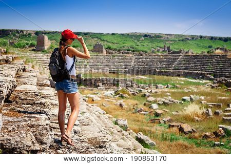 Pretty Tourist Woman With Backpack At The Ruins Of Ancient City Of Perge Near Antalya Turkey