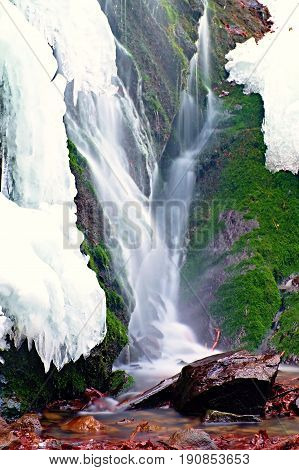 Winter View To Cascade Of Waterfall, Icy Snow On The Rocky Wall And Boulders In Rapid Stream. Reflec