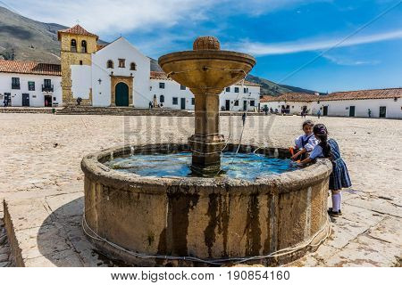 Villa De Leyva, Colombia  - February 8, 2017 : children playing at the fountain of Plaza Mayor of  Villa de Leyva Boyaca in Colombia South America