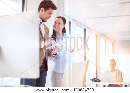 Business people using digital tablet with female colleague in background at office
