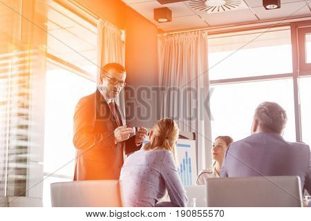 Mature businessman discussing with colleagues in board room