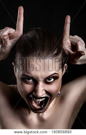 fun luxury woman making devil horns screaming on black background