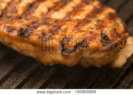 preparing chicken breast on a pan grill closeup