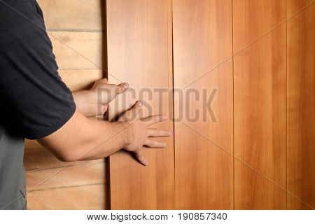 A Man In Construction Clothes Mounts Medium Density Fiberboard Panels On The Wall