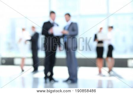 Confident business partners working in office and talking. Blurr