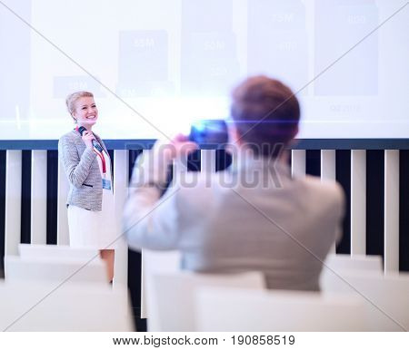Rear view of businessman photographing female public speaker in seminar hall