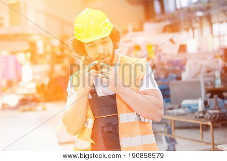 Young manual worker wearing protective clothing while using walkie-talkie in metal industry