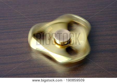 Golden metal fidget spinner spinning on table