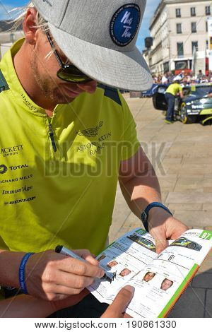 LE MANS, FRANCE - JUNE 11, 2017: Famous Danish racer Nicki Thiim gives the autograph on his photo World champion