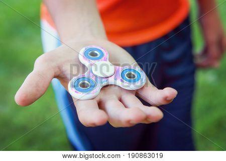 Teen boy with a fidget spinner outdoors, shallow focus