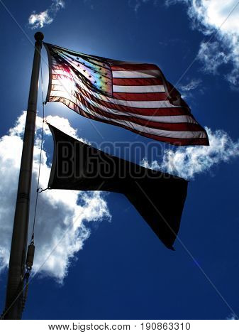 American Flag on flagpole pole blue sky and clouds windy day
