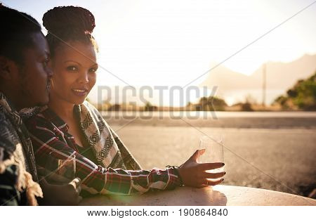 Powerful image of graceful and beautiful young woman of african descent looking at the camera during a date with her male partner, proud of her accomplishments, and courageous in life.