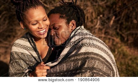 Mixed race woman being embraced by her african boyfriend outdoors covered by a blanket at a park during golden hour at sunset, bonding and getting to know each other.