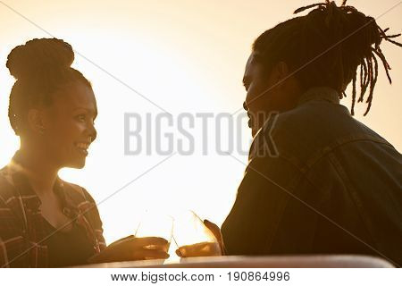 Couple making a toast with some alcoholic beverages, silhouetted by the sunset golden hour behind them, both of african descent, the mixed race woman loves her african man's attention.