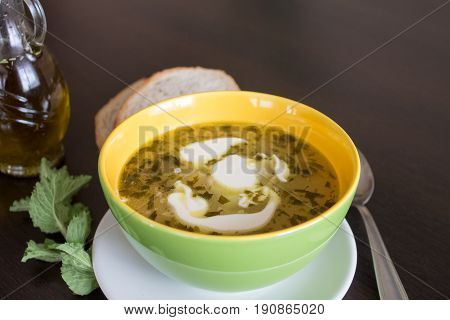 Potato and tarragon soup with cream on dark wooden background.