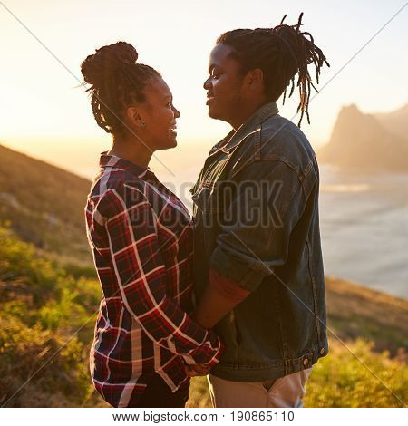 Square image of a mixed race woman and an african man holding hands while facing each other on an outdoor date durind golden hour at sunset with ocean and mountains in the landscape behind them.