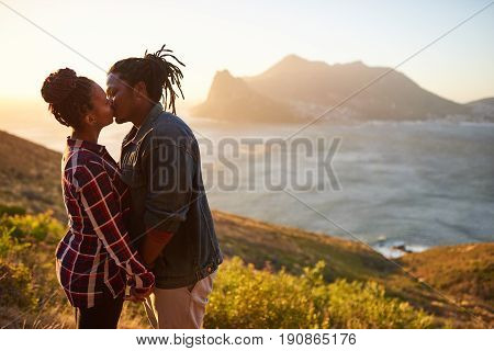 Authentic interracial couple dressed casually, kissing affectionately while facing one and other and holding hands with ocean and mountains in the view behind them.