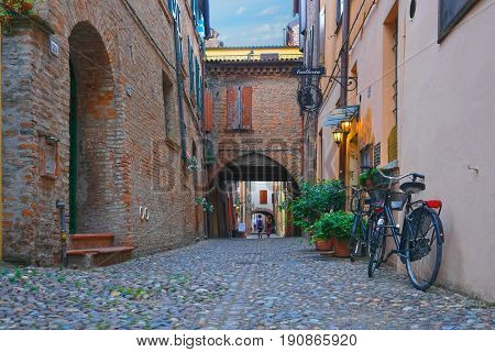 Ferrara, Italy - June, 3, 2017: Bicycle parked near the wall of an ancient house in an Old Town of Ferrara, Italy