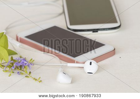 two mobile and earphone on background white