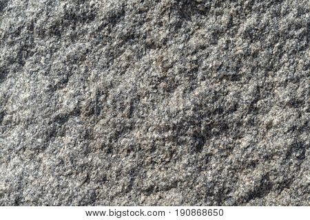 The rough surface of a granite piece of stone. Seen small rocks and bumps. Granular surface with pits and tubercles.