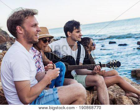 group of young and cheerful friends sitting on stones on beach. One man is playing guitar. Music on Wild beach