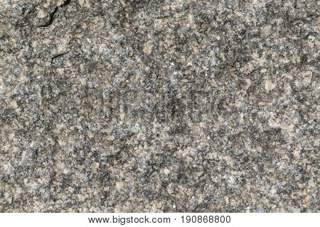 The rough surface of a granite piece of stone. Seen small rocks and bumps. Granular surface with pits and tubercles. There are cracks and vyscherbliny.
