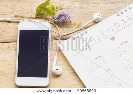 mobile with earphone and calendar on background wood