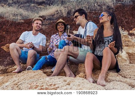 group of young and cheerful friends sitting on stones on beach. One man is playing guitar. Wild beach. Happy youth time with music