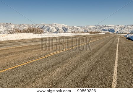 Paved plowed and dry road in Utah with snow in the mountains and a clear blue sky