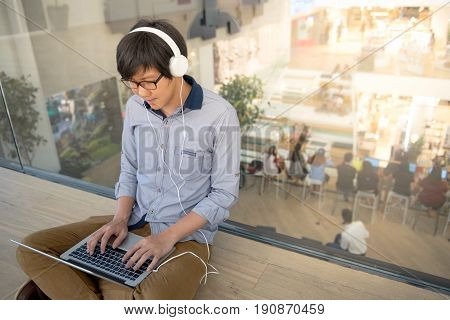 Young Asian man dressed in casual style working with his laptop while listening to music. Digital nomad working in co working space modern IT lifestyle with work life balance concept.