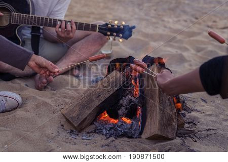 Closeup view of young and cheerful friends sitting on beach and fry sasuages or weenies in bonfire One man is playing guitar. Music on Wild beach