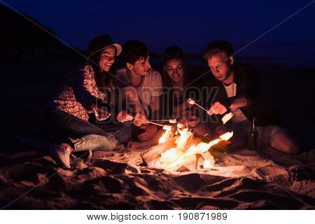 young and cheerful friends sitting on the beach and fry marshmallows near bonfire They look happy and smiling. Night time
