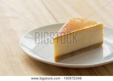 Homemade New York style cheese cake on white plate. Moist and smooth baked cheese cake. Delicious plain New York cheese cake with golden brown surface on rustic wood table with copy space for background. Triangle slice piece of cheese cake.