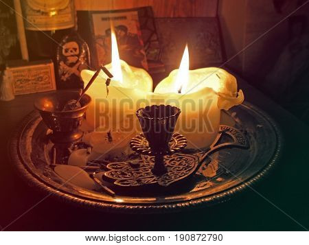 Two candles and incense arranged on a plate