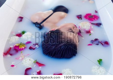 Closeup view of Woman in bath. Sexy brunette woman relaxing in hot milk bathtube with flowers. she is wearing black sexual lingerie. Spa satisfaction poster
