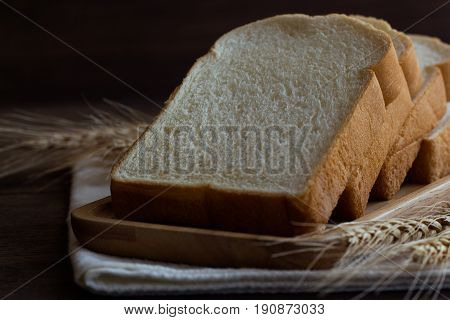 Sliced bread stack on wood plate. Homemade bread for breakfast put on rustic wood table. Soft and sticky homemade bread for delicious toast in breakfast. Homemade bakery background with copy space. Sliced bread in underexposure concept.