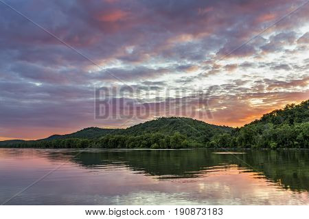 A colorful sunset sky is reflected on the Ohio River as photographed from the shore at Paden City West Virginia looking across to the Ohio side of the river.