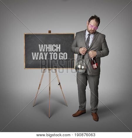 Which way to go text on blackboard with businessman and key