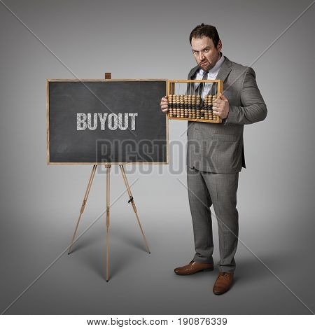 Buyout text on blackboard with businessman and abacus