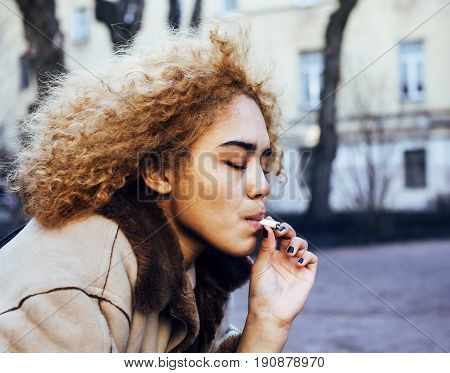 young pretty girl teenage outside smoking cigarette close up, looking like real junky, social issues concept idea