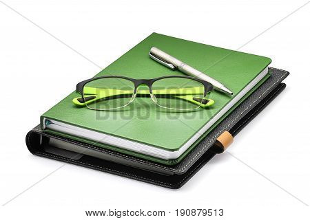 green notebook with green glasses and silver pen isolated on whtie background office concept