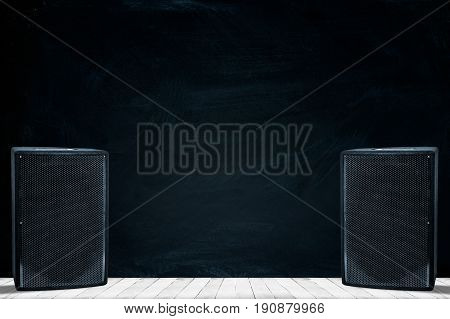 Large black speakers on wooden background with space for text writing.