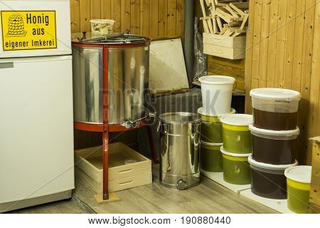 buckets full of extracted honey out of acentrifuge and other Beekeeper equipment - yellow german sign saying homemade honey